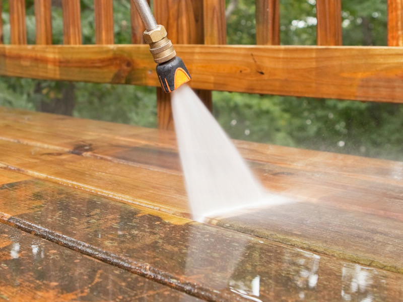 Pressure washing a timber deck, Spain